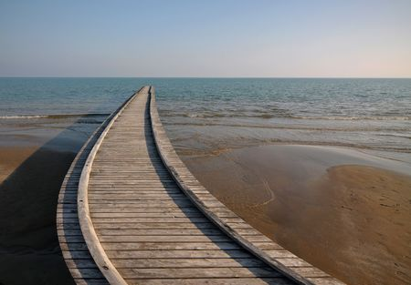 wood railroads: Digitally manipulated image of a wooden pier on the seashore. Stock Photo