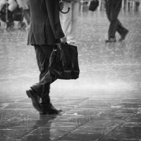 Unrecognizable business man walking in the rain
