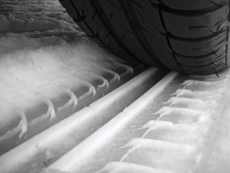Car tyre trace on snow surface photo