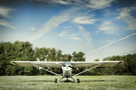 Small airplane parked in a meadow photo