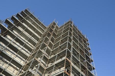 andamios: Andamios que rodea un edificio en una obra en construcción