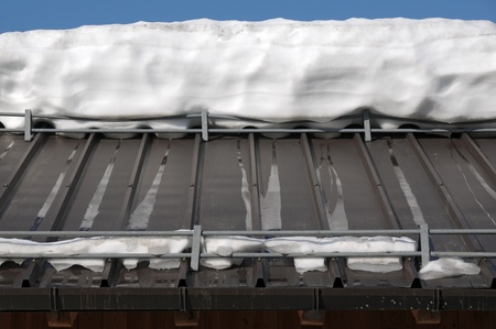 thawing: Alpine house roof detail with thawing snow