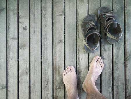 Pies de los hombres y las sandalias de piso de madera Foto de archivo - 11709974