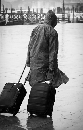 slicker: Unrecognizable tourist walking with his luggages in Venice during a downpour