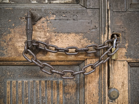 Closed lock with a chain on an old wooden door Stock Photo - 13496998