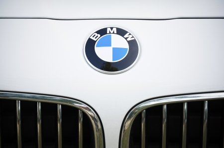 Padua, Italy - July 8, 2012: Circle shape BMW logo and part of the front grill on a white BMW (3 Series) car. BMW is a German automobile manufacturer. Shot in a public parking in Padua, Italy.