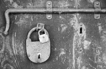 Old padlocks and bolt on an ancient rural house entrance door Stock Photo - 17176853