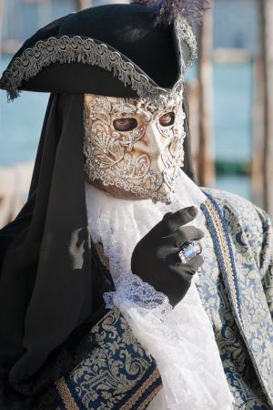 mystery man: Venice, Italy - February 17, 2012: Mask posing along Saint Mark waterfront during famous Venetian Carnival celebrations. Shot in Venice, Italy