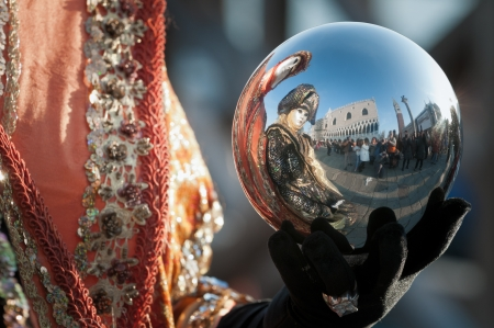 Venice, Italy - February 12, 2010: Saint Mark square reflections on a metallic sphere in the hands of a mask during famous Venetian Carnival celebrations. Shot in Venice, Italy