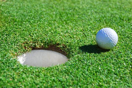 Golf Ball Next to Cup with Shallow Depth of Field Stock Photo