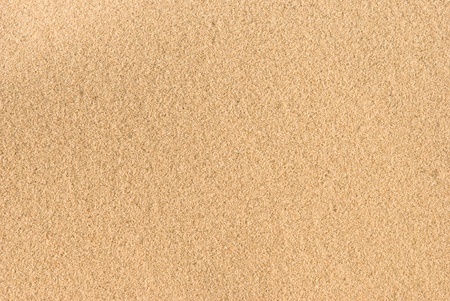 A frame-filled background of sand on a beach. Stock Photo