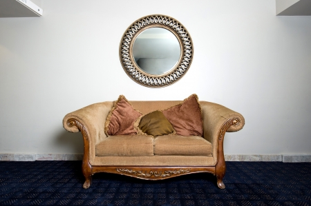 Couch and Mirror Against Wall Stock Photo