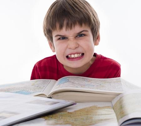 angry child: boy hates reading Stock Photo
