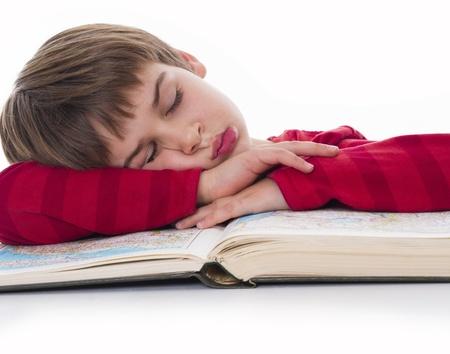 少年は本に眠っています。 写真素材