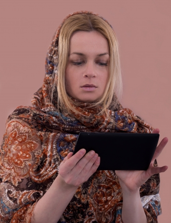 woman with oriental headkerchief using tablet, traditional and modern,  Stock fotó
