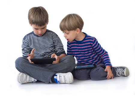 Boys playing computer games on tablets photo