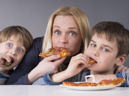 Hungry family, mother and son eating pizza