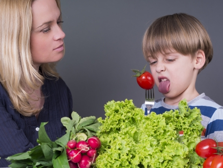 Mother trying to feed her little son with tomato photo