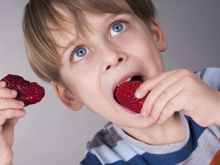 Cute boy eating strawberries Stock Photo