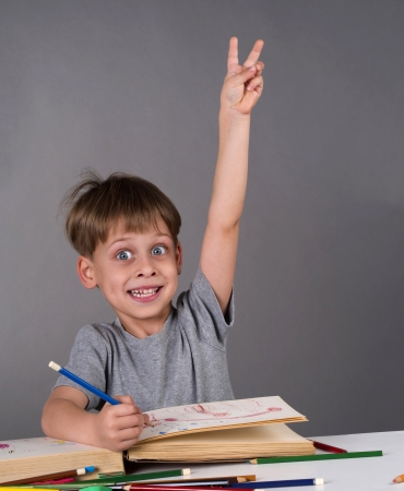 enthusiastic schoolboy raising their hands to give an answer, education concept  photo
