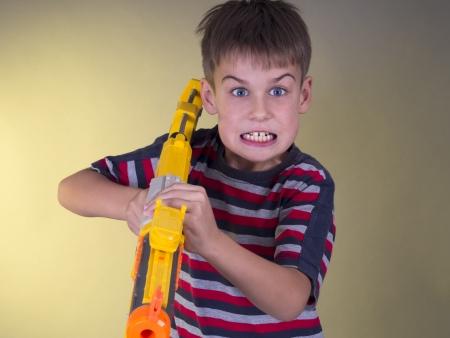 playful behaviour: boy with toy gun