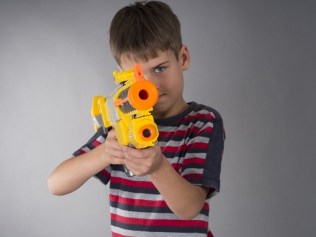 ni�os malos: chico con pistola de juguete Foto de archivo