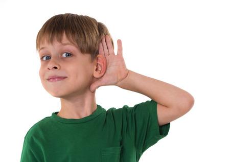 何かを聞いている若い少年 写真素材