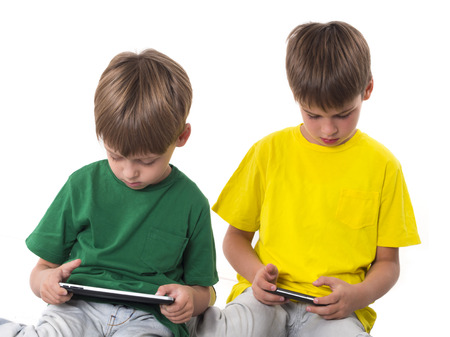 kid pointing: boys playing video games on tablets Stock Photo