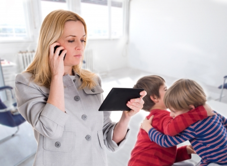 busy mother with tablet and mobile while her children fighting Zdjęcie Seryjne - 23932222