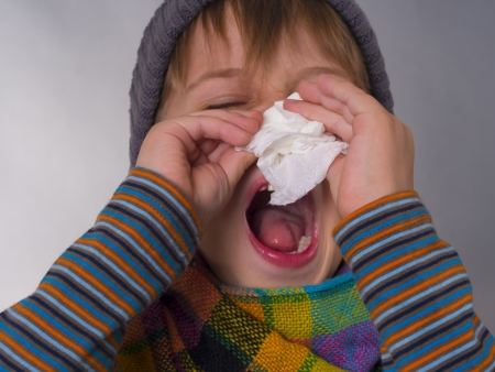 Kid wipes a nose with napkin