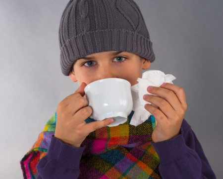snotty: Beautiful child drinking tea and wiping a nose with napkin
