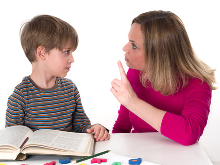 hostility: young pupil doesn t want to learn, he confronts his mother who is threatening him  Stock Photo