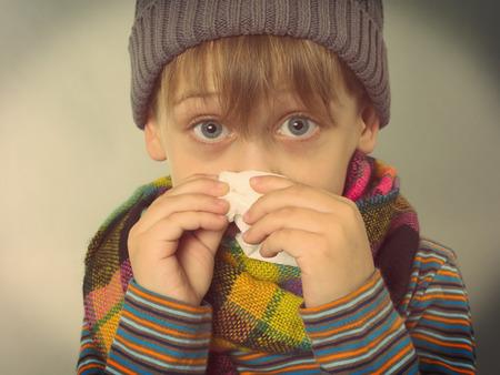 gripe: muchacho que limpia su nariz Foto de archivo