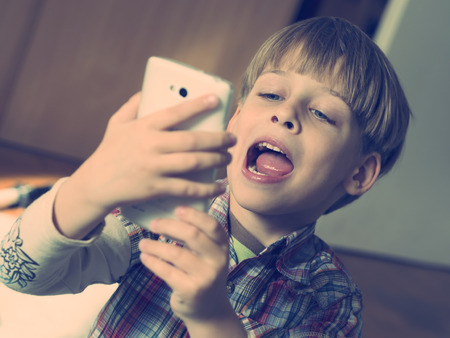 boy taking selfie with smartphone photo