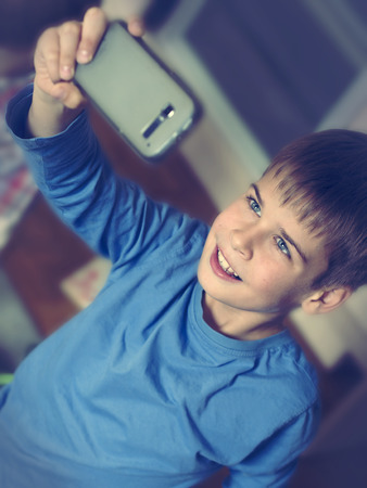 boy taking selfie with smartphone photo