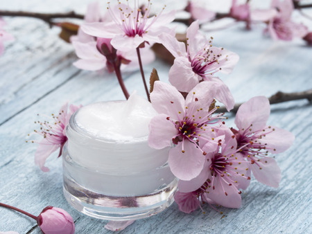 containers: natural facial cream with spring flowers decoration