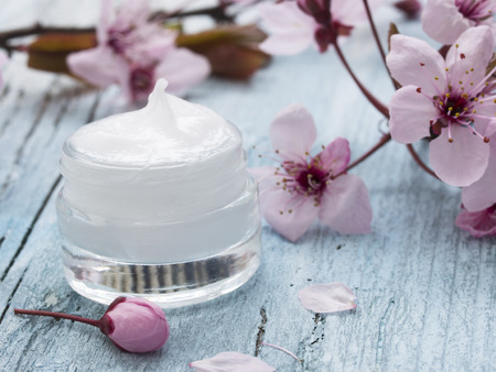 skincare: natural facial cream with spring flowers decoration