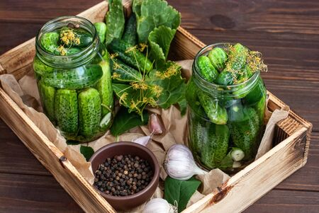 Fermentation of cucumbers in glass jars. Raw cucumbers, dill flowers, cherry leaf, horseradish leaf, spices and herbs on a tray, concept of organic and healthy nutrition, pickling cucumbers.