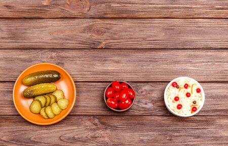 Homemade fermented milk products on a plate - sauerkraut, pickled tomatoes, pickles on a wooden background. Copy space, flat lay. Ukrainian light meal. View from above.