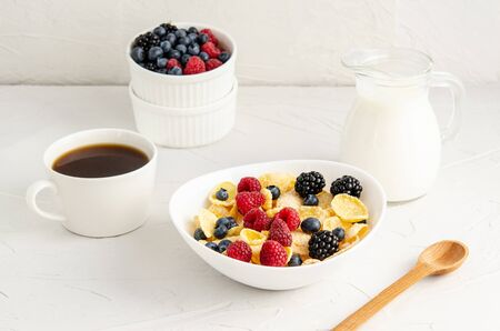 Healthy breakfast with cornflakes in a white plate, berries, milk and coffee on a white background. Copy space for your text, flat lay, healthy snacks, quick breakfast. Close-up. Foto de archivo