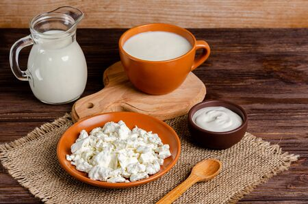 Homemade fermented milk products - kefir, cottage cheese on a wooden background. The concept of a healthy diet. Ferment for yeast bacterial fermentation, intestinal health concept.