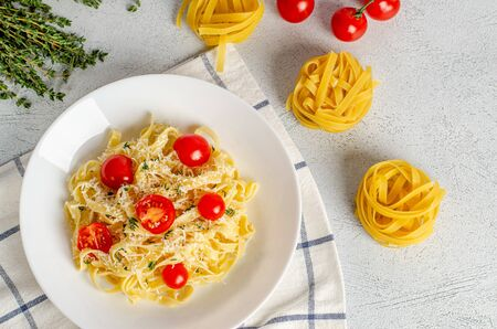 Homemade tagliatelle pasta with tomatoes, thyme, parmesan cheese in a white plate on a light background. Flat lay. Proper nutrition, diet. View from above