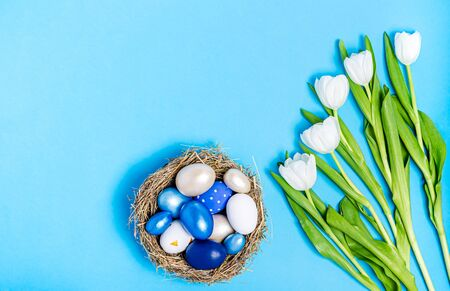 Easter eggs of blue flowers in a decorative nest of straw and a bouquet of white tulips on a blue background, copy space, flat lay. Place for text. The concept of the holiday, spring. View from above.