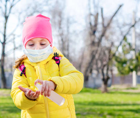 A little girl in a protective mask to protect against air pollution and the Covid-19 virus uses a hand sanitizer to prevent infection by viruses and bacteria. Banque d'images