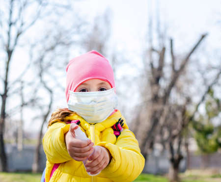 Little girl in a protective mask to protect against air pollution and viral Covid-19 holding a disinfectant hand sanitizer to prevent the infection by viruses and bacteria.