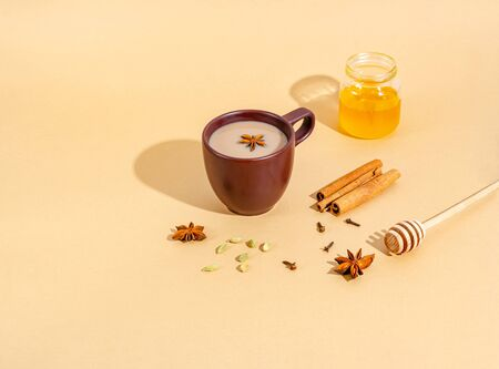 Traditional indian tea. Masala tea in a dark clay cup with ingredients, hard shadows. Cinnamon, cardamom, anise, honey, cloves on a beige background. Close-up. Copy space for text, flat lay. Zdjęcie Seryjne