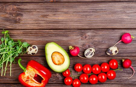 A variety of healthy and natural products on a wooden background. Radishes, tomatoes, sweet peppers, avocados, quail eggs, microgreen, top view. Healthy food, diet. Flat lay, place for text.