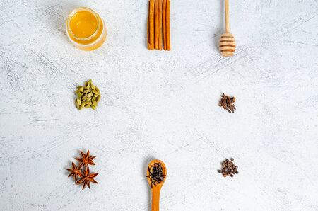 Ingredients in the form of a frame for the preparation of the Indian traditional drink masala tea. Cinnamon, cardamom, anise, honey, cloves, dry tea on a light background. View from above. Copy space,