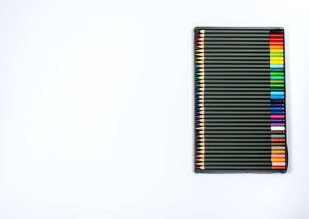 Colored pencils in a case on a white background close-up with place for text. The concept of pencils creativity, hobbies, activities. Flat lay, copy space, space for text. View from above. Standard-Bild