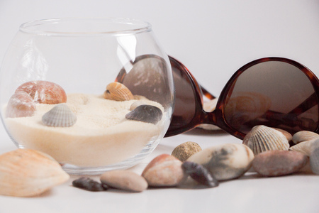 A composition of sand, sea stones and seashells, the sea on the table, the summer will come soon, the dreams of the sea